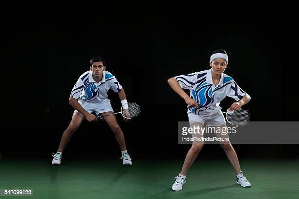Man and woman playing badminton doubles