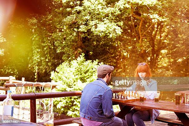 man and woman playing chess in beer garden