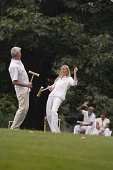 Man and woman playing croquet with couple watching