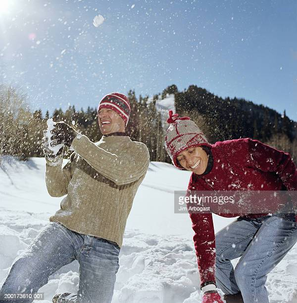 Man and woman playing in snow, smiling