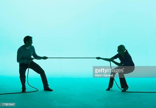 Man and woman playing tug of war