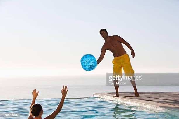 Mann und Frau spielen mit ball im Swimmingpool