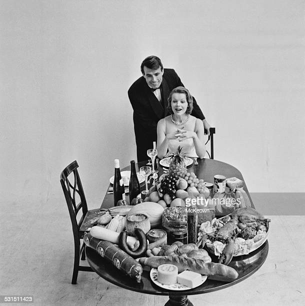 A man and woman pose at a table laden with food at the British Food Fair Olympia Exhibition Hall London 25th August 1958
