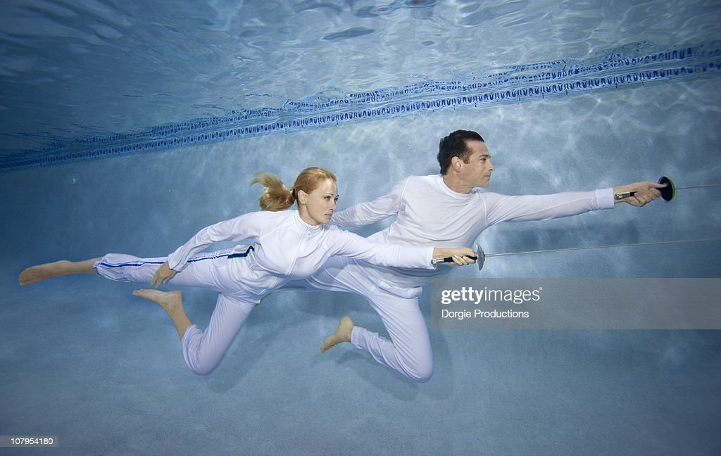 Man And Woman Practice Fencing Techniques Underwat Stock