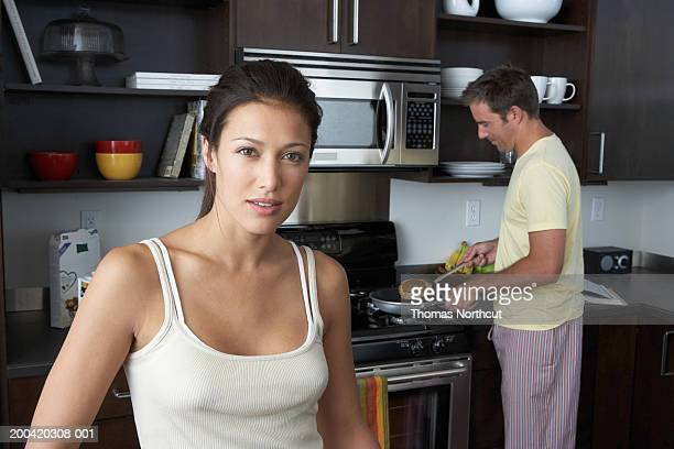 Man and woman preparing breakfast (focus on woman in foreground)