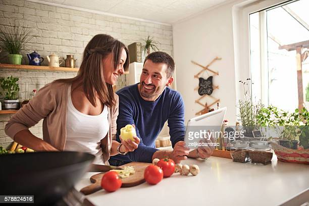 Man and woman preparing dinner using tablet