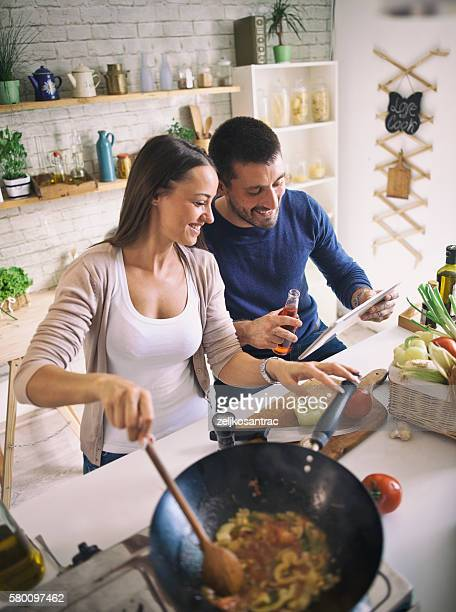 Man and woman preparing dinner using tablet