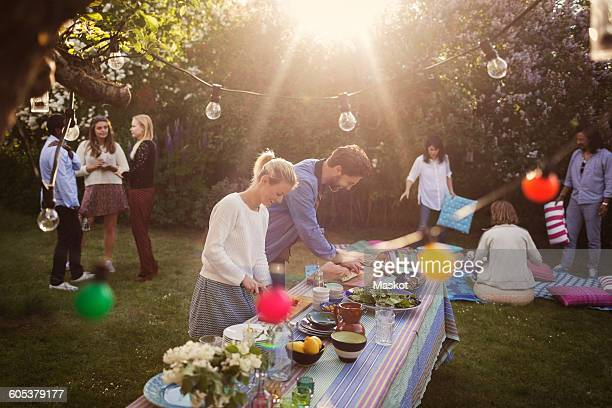 Man and woman preparing food at dining table with friends in background during summer party