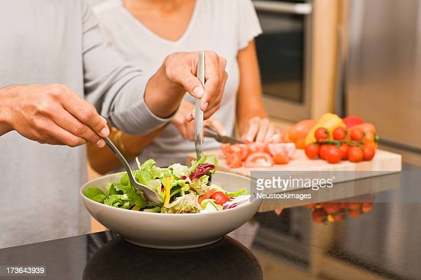 Man and woman preparing salad in kitchen