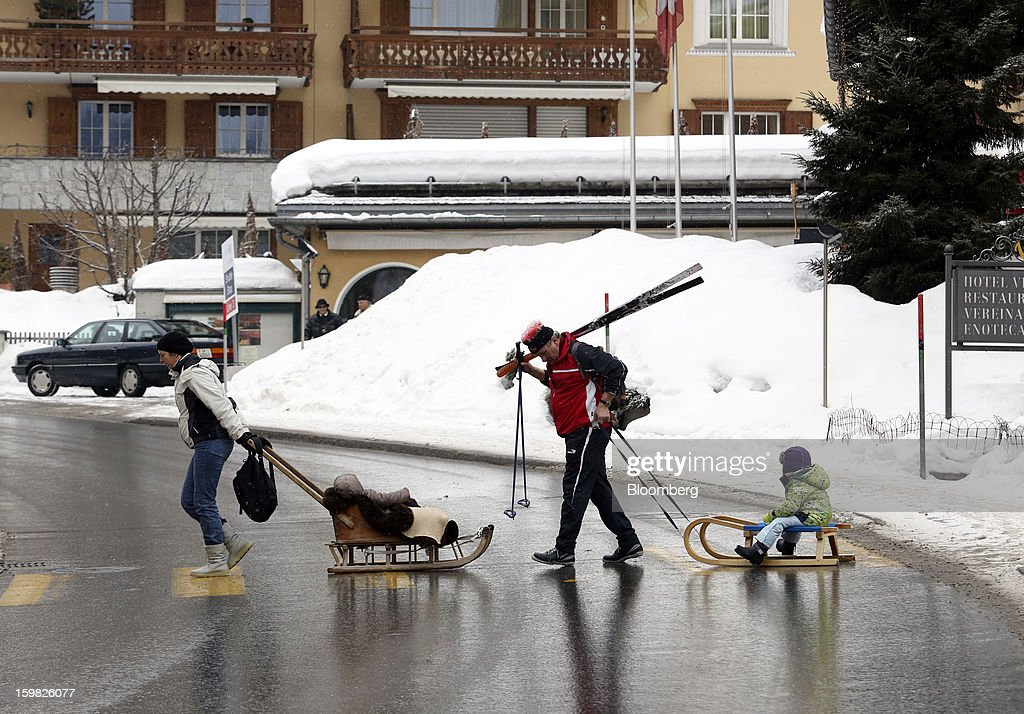 A man and woman pull two children across a pedestrian crossing as they sit on wooden sledges in Klosters, Switzerland, on Monday, Jan. 21, 2013. This week the business elite gathers in the Swiss Alps for the 43rd annual meeting of the World Economic Forum in Davos, the five day event runs from Jan. 23-27. Photographer: Chris Ratcliffe/Bloomberg via Getty Images