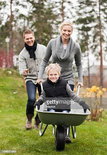 Man and woman pushing son on wheelbarrow in back yard
