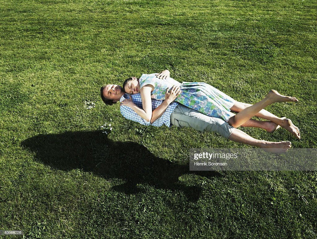 Man and woman realxing floating above the grass