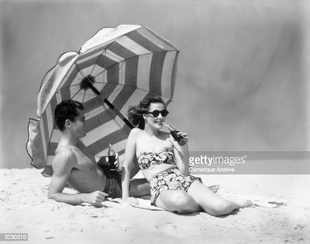 A man and woman recline on the beach drinking bottles of cola under a striped parasol 1950s They wear swimsuits