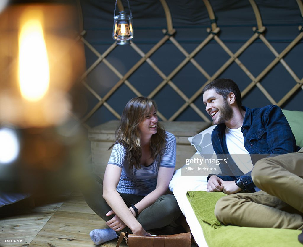 Man and woman relaxing around bed inside yurt. : Stock Photo