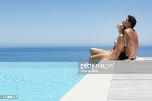 Man and woman relaxing on infinity pool deck in swimsuits