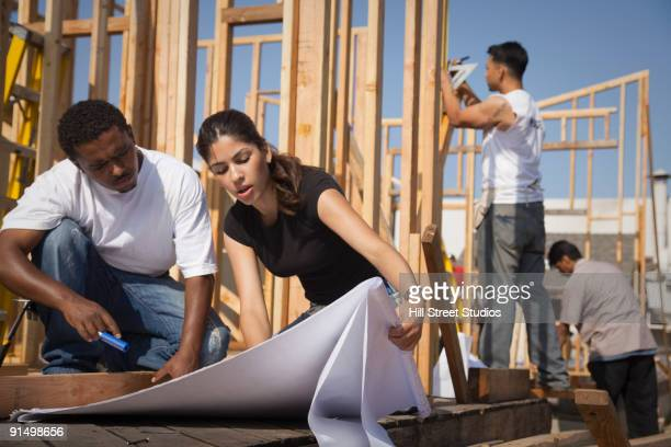 Man and woman reviewing blueprints at construction site