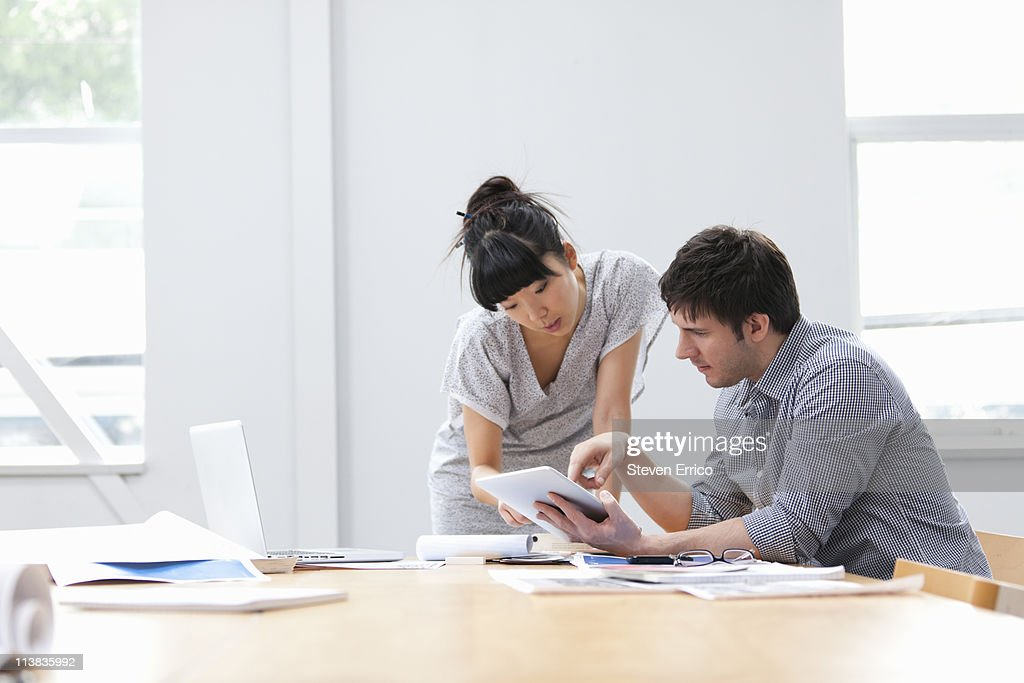 Man and woman reviewing work on digital tablet : Stock Photo