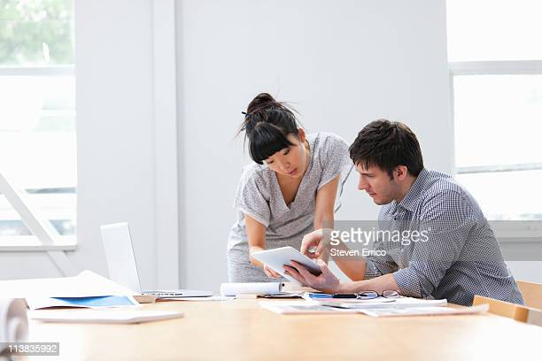 Man and woman reviewing work on digital tablet