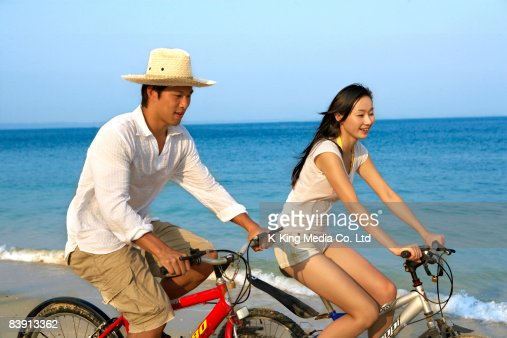 Man and woman riding bicycles on beach. : Stock Photo