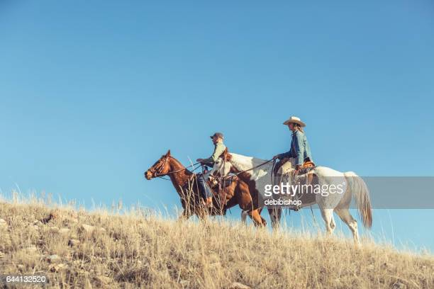 Man And Woman Riding Horseback Up Grassy Hill