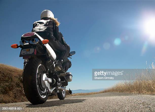 Man and woman riding motorcycle, rear view