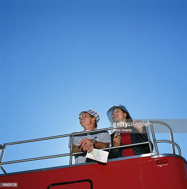 Man and woman riding on top deck of double-decker bus, low angle view