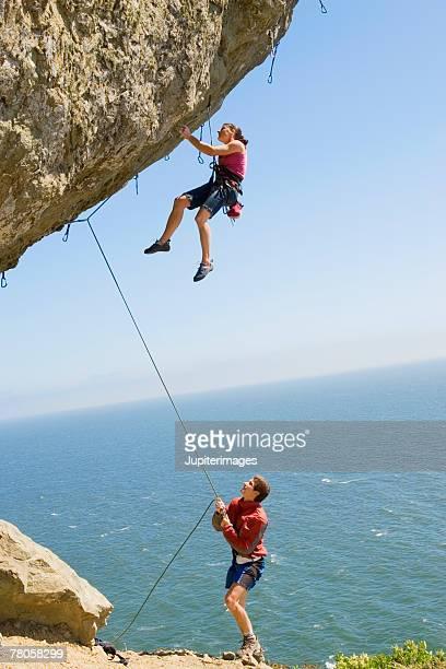 Man and woman rock climbing