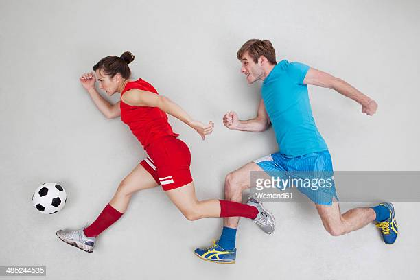 Man and woman running after football