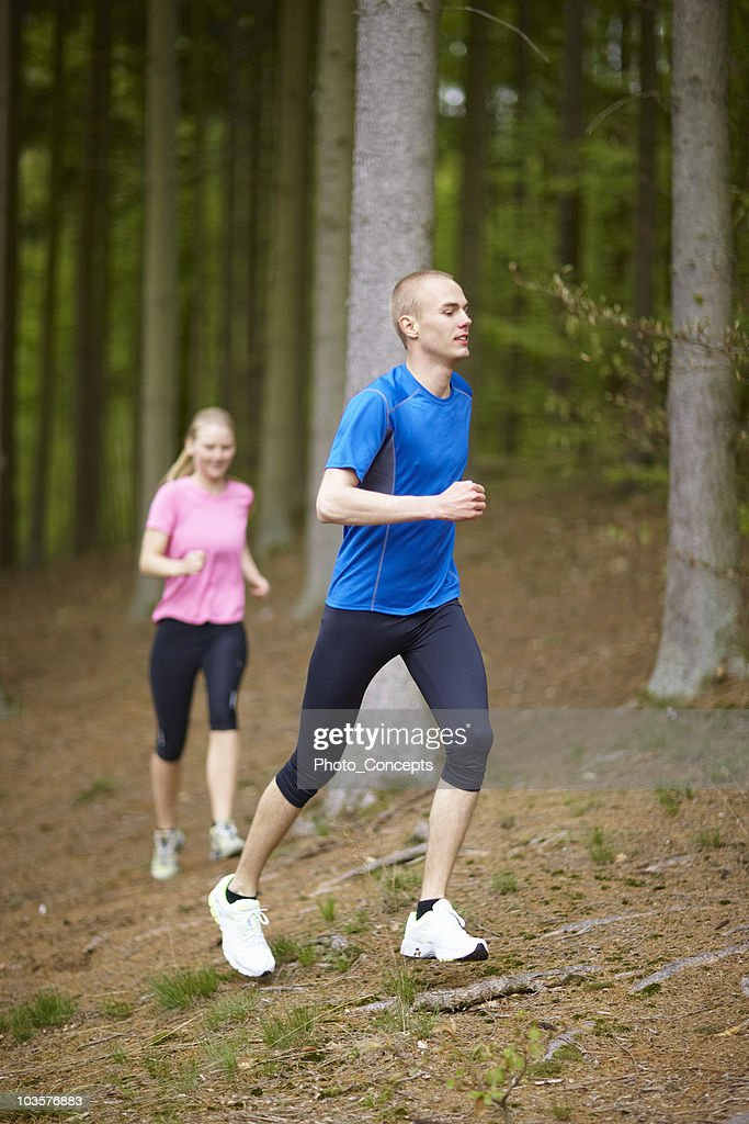 Man and woman running in forest : Stock Photo