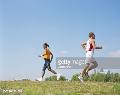 Man and woman running in opposite directions through field
