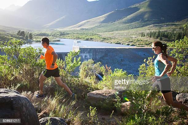 Mann und Frau Laufen am frühen Morgen in den Bergen