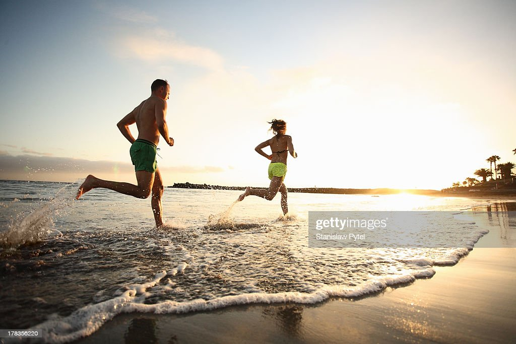 Man and woman running on beach at sunset : Stock Photo