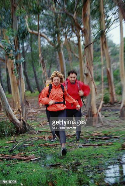 Man and woman running through forest