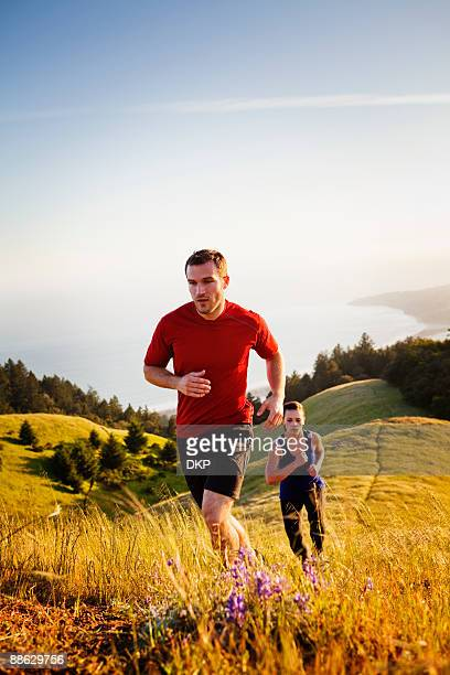 Man and woman running up grassy trail.