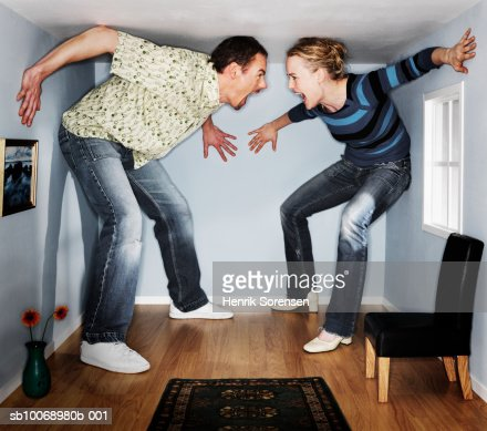 Man and woman screaming at each other in small living room : Stock Photo
