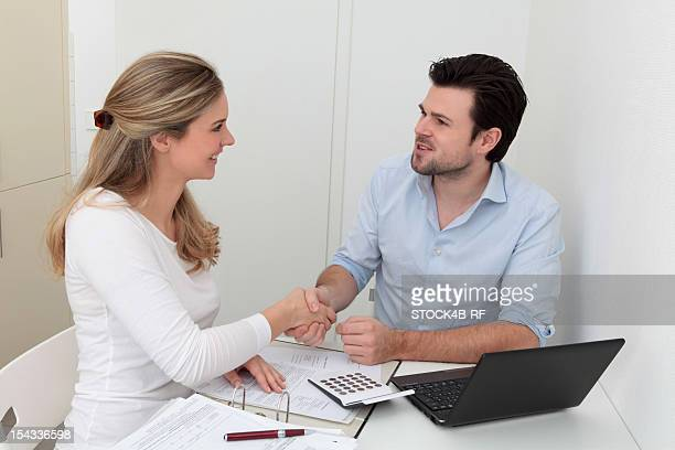 Man and woman shaking hands at table with file, calculator and laptop