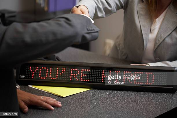Man and woman shaking hands over LED sign saying you're hired in office