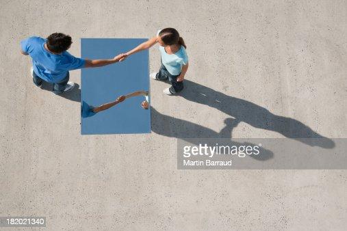 Uomo e donna si stringono la mano con specchio e riflessione su terra foto stock getty images - La mano sullo specchio ...