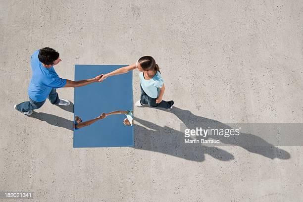 Homme et femme se serrant la main avec le miroir au rez-de-chaussée et réflexion