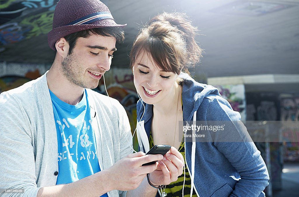 man and woman sharing music on mobile : Stock Photo