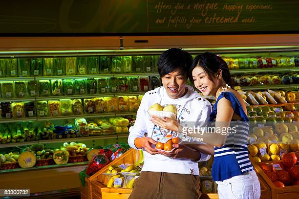 Man and woman shopping for fruit at supermarket
