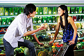 Man and woman shopping for produce in supermarket