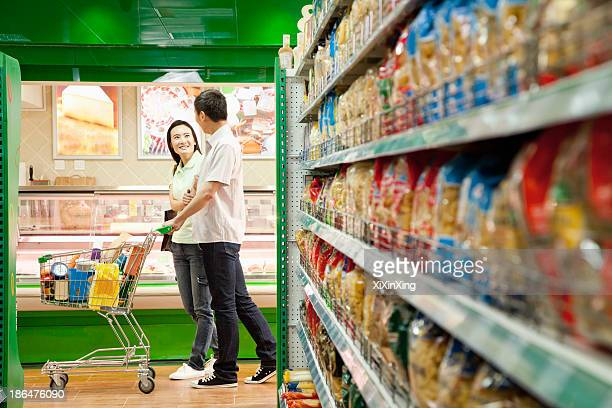 Man and Woman Shopping in a Supermarket with Shopping Cart