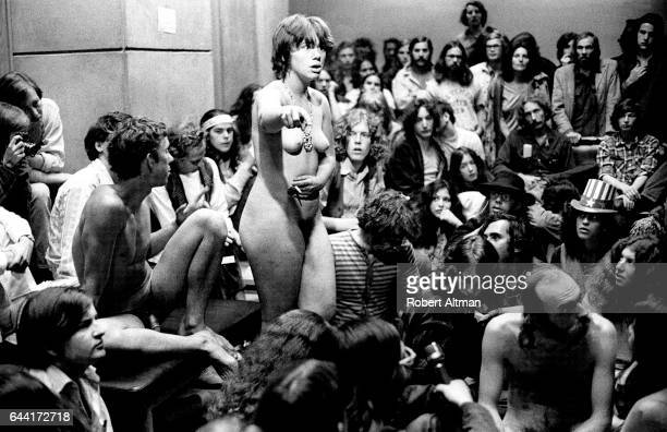 A man and woman sit and stand naked in front of a group of people during a meeting on the last day of The Alternative Media Conference on June 20...