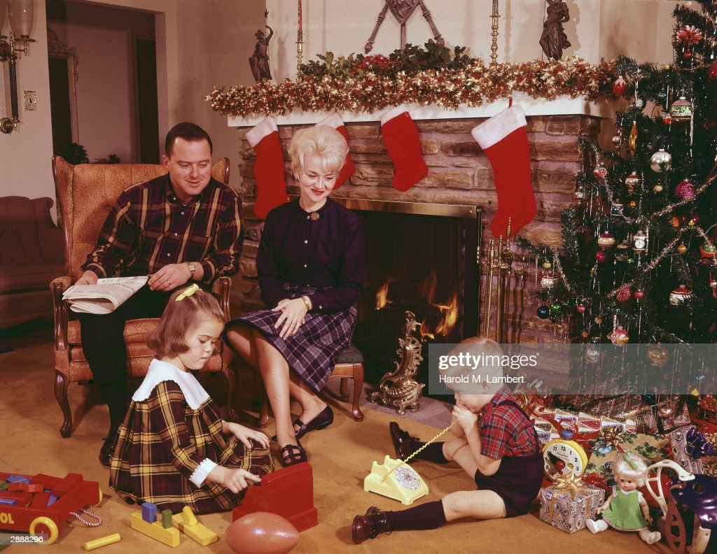 family sitting by fireplace on christmas pictures getty images