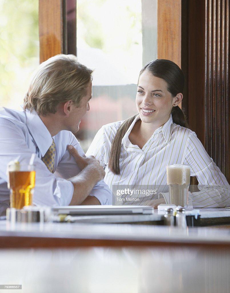 Man and woman sitting at a bar talking : Stock Photo