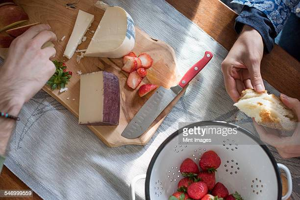 Man and woman sitting at a table with a wooden chopping board with a selection of cheeses, strawberries and bread.