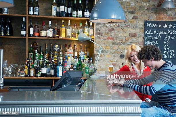man and woman sitting at bar with champagne