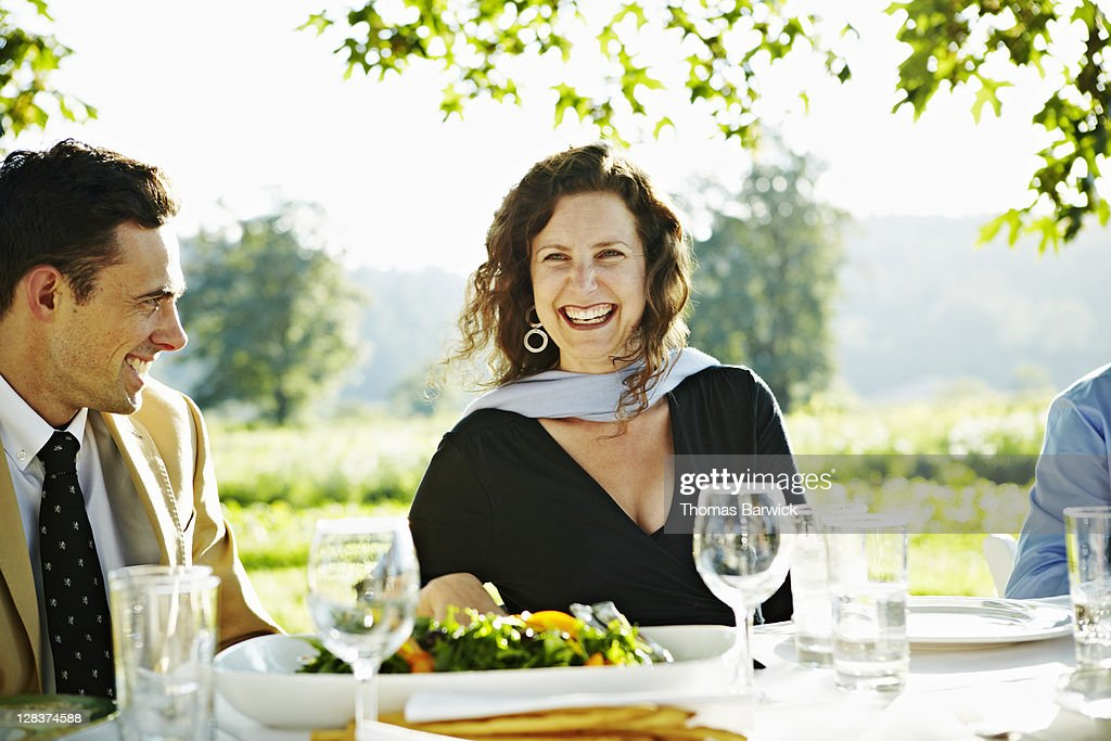 Man and woman sitting at outdoor table laughing : Stock Photo