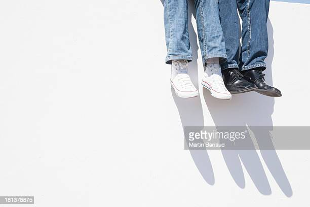 Man and woman sitting atop wall